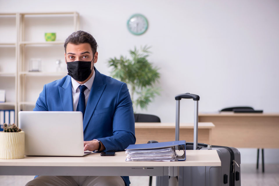 мужчина в маске сиди за ноутбуком